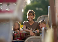 BANTAM, CT- 24 JULY 2008- 072408JT02-.From right, Owen Morse, 5, of Bantam, rides the Ferris Wheel with his mother Robin, Mckayla Thomas, also 5, of Morris, and Owen's twin brother Quinn (partially obscured) at the Bantam Fire Carnival on Thursday in Bantam. .Josalee Thrift / Republican-American