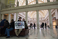 Robert Meringolo, from Albany, NY, holds a protest sign inside Union Station the morning of the Presidential Inauguration. The last time he protested here was, he said, in 1969.<br />