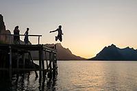 Person jumps from wooden pier into Reinefjord on summer evening, Moskenesøy, Lofoten Islands, Norway