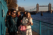 Young women walking together along the north side of the river Thames near to Tower Bridge. The north river path provides an interesting and different view to the south bank.