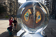 Children amazed at a distorted face through Petroc Sesti's art instillation called Time Fold in Great Helen's Square, in the City of London. The kids look at the optics with amazement, marvelling at its bending of light and optical experience. Petroc Sesti is a London based British artist and Time Fold bends light like a prism, hypnotising the viewer by reflecting on its ever-changing spiral motion.