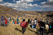 """The crowd swarms over a hill at Sacsayhuamán to view the ceremony moments after the police cordon was mobbed by local people. Inti Raymi """"Festival of the Sun"""", Sacsayhuamán, Cusco, Peru."""