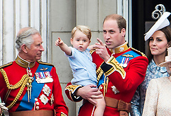 © London News Pictures. 13/06/2015. London, UK. L to R Prince Charles,  Prince George of Cambridge being held up by his father Prince William, Catherine Duchess of Cambridge.  Members of the Royal Family on the balcony of Buckingham Palace during the annual Trooping the Colour Ceremony in central London. The event marks the queens official birthday. .Photo credit: Ben Cawthra/LNP