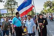"""01 FEBRUARY 2014 - BANGKOK, THAILAND: A Thai Muslim woman carries a Thai flag to confront anti-government protestors that were preventing her from voting. She wanted to vote and was upset when protestors shut her polling place. Thais went to the polls in a """"snap election"""" Sunday called in December after Prime Minister Yingluck Shinawatra dissolved the parliament in the face of large anti-government protests in Bangkok. The anti-government opposition, led by the People's Democratic Reform Committee (PDRC), called for a boycott of the election and threatened to disrupt voting. Many polling places in Bangkok were closed by protestors who blocked access to the polls or distribution of ballots. The result of the election are likely to be contested in the Thai Constitutional Court and may be invalidated because there won't be quorum in the Thai parliament.    PHOTO BY JACK KURTZ"""