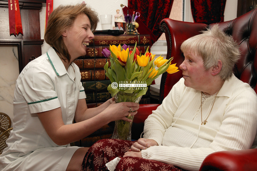 Woman at home with a carer holding a vase of flowers; homecare for the disabled,