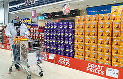 © Licensed to London News Pictures. 14/04/2020. London, UK. A shopper wearing a face mask walks past a large selection of unsold Easter Eggs at Sainsbury's supermarket in north London. The government had ordered people to 'Stay home this Easter' during coronavirus lockdown to slow the spread of COVID-19 and reduce pressure on the NHS. Photo credit: Dinendra Haria/LNP