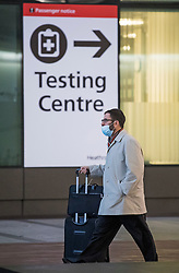© Licensed to London News Pictures. 15/02/2021. London, UK. A man pushing his luggage walks past a sign for a COVID-19 test centre at Heathrow Airport, Terminal 2 in London. New quarantine measures being introduced from today mean that any travellers form red list countries will be required to isolate for ten days in a hotel at a cost of £1,750 per person.  Photo credit: Ben Cawthra/LNP