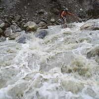 TIBET, Tsangpo Gorge, David Breashears fords rain- swollen side stream from Namche Barwa Glac., Himalaya
