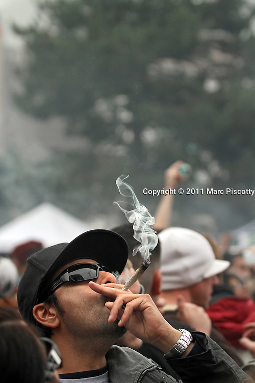SHOT 4/20/11 4:22:13 PM - Marijuana enthusiasts light up in unison at 4:20pm at the 420 Rally in Denver, Co. They converged upon Denver, Colorado and Civic Center Park for an event that has come to symbolize Colorado's burgeoning claim as the nation's cannabis capital. Denver's annual April 20th pro-marijuana smoke-out -- known as the 420 Rally -- is reputedly the largest of its kind in the world on a day that has come to be regarded as a ganja holiday. The crowd was estimated at about 10,000 participants and the signature moment of the rally occurred at 4:20 p.m., when participants collectively lit up and a thick cloud of marijuana smoke rose over the park within site of the state capital. Organizers say the goal of the rally is to bring people together to protest peacefully marijuana prohibition. (Photo by Marc Piscotty / © 2011)