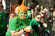 A parade watcher in green, with orange highlights.