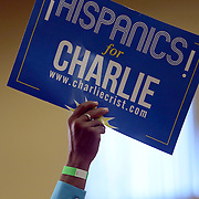 """A supporter holds up a sign that says """"Hispanics for Charlie"""" at the """"Commit to Vote"""" rally for Democrat Charlie Crist who is running for Governor of the state of Florida. The campaign called on the event to """" energize voters and lay out the stakes for Floridians in the critical election on November 4th."""" at the Barnett Park Gymnasium in Orlando, Florida on Friday, Nov. 17, 2014. (AP Photo/Alex Menendez)"""