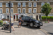 A stationary black Volkswagen car on two wheels after driving into a bollard on Railton Road on the 24th July 2019 in South London in the United Kingdom.