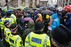 London, UK. 14 October, 2019. Police officers attempt to disperse climate activists from Extinction Rebellion who had been occupying the busy junction in front of the Bank of England since 7am on the eighth day of International Rebellion protests.