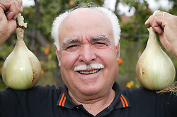 Elderly man with home grown onions,