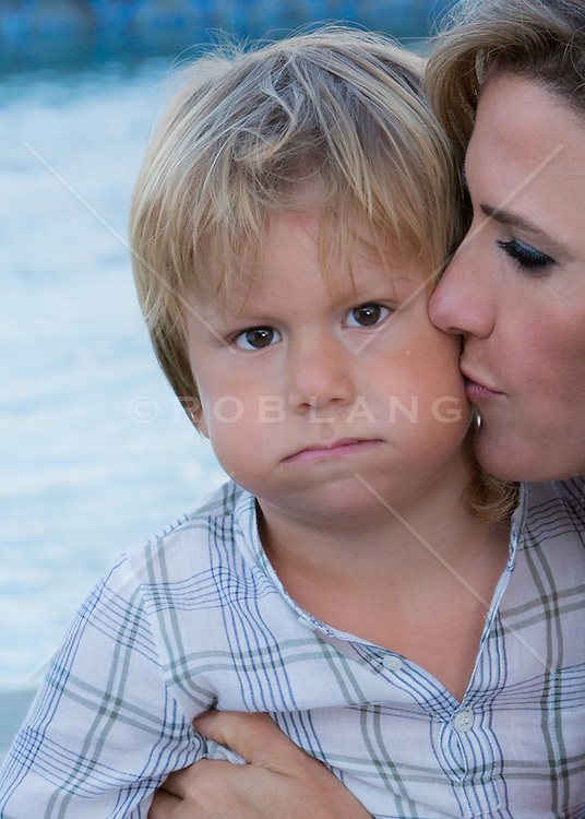 mother kissing the cheek of her little boy