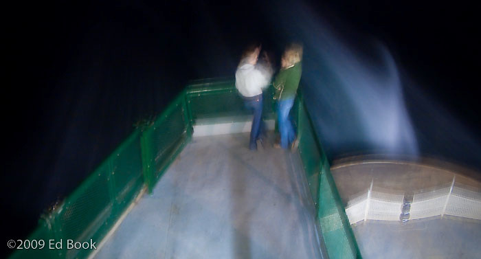two women communicating animatedly on the ferry in an abstract scene at night.