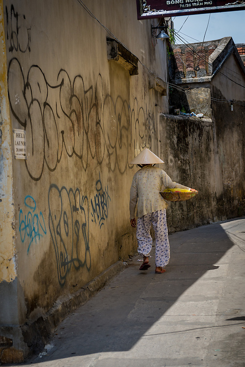Elderly Vietnamese woman walking through narrow street in Hoi An ancient town