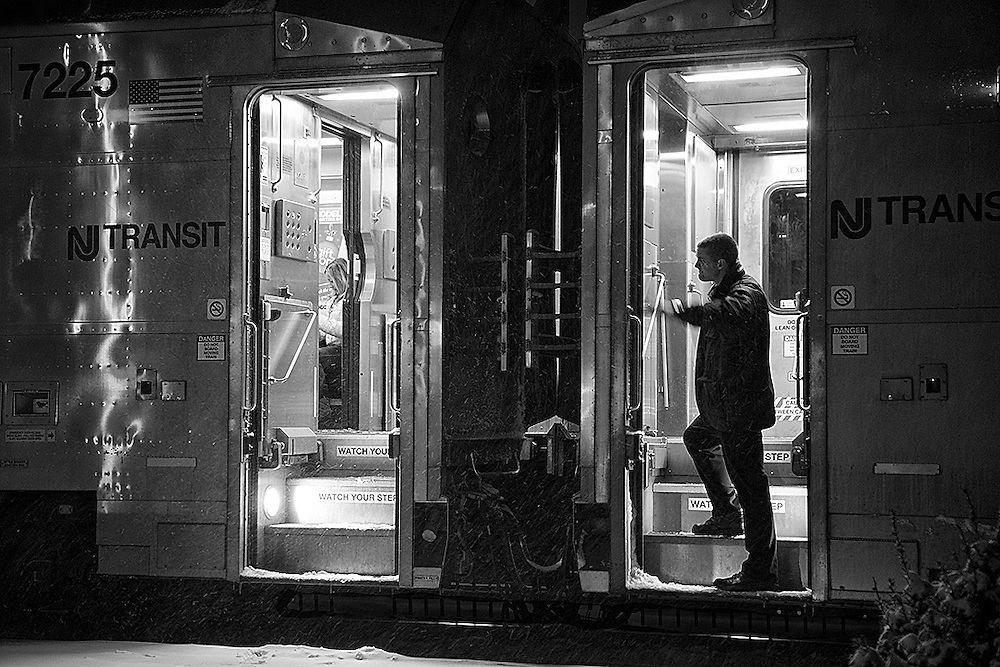 During a station stop at Short Hills station, a conductor on a New York bound train signals to his crew that the train is safe to move.