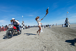 Flag girl gets the races going right from the start during the Chris Price on his 1941 Indian Scout at the Race of Gentlemen. Wildwood, NJ, USA. October 11, 2015.  Photography ©2015 Michael Lichter.