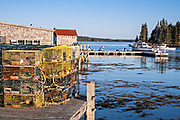 Lobster docks and pier piled high with traps in the quaint fishing harbor of Port Clyde, Maine.