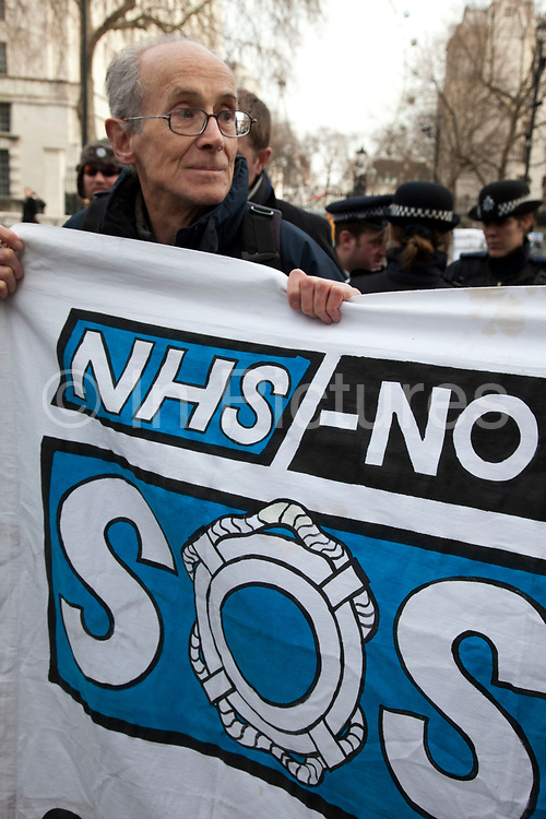 Protesters gather outside on Whitehall in a demonstration called 'Summit of the Uninvited', Downing Street, London, UK. Outside the Prime Minister's summit meeting where he invited selected health professionals and private companies to discuss implementation of the health bill and the future of the NHS and excluded all the organisations critical of the bill. <br /> <br /> It has been alleged this shows the government's desperation that they have had to rapidly convene this meeting to try to cobble this together at the last minute to try to show they still have some professional support and to split the profession and marginalise those who are critical.