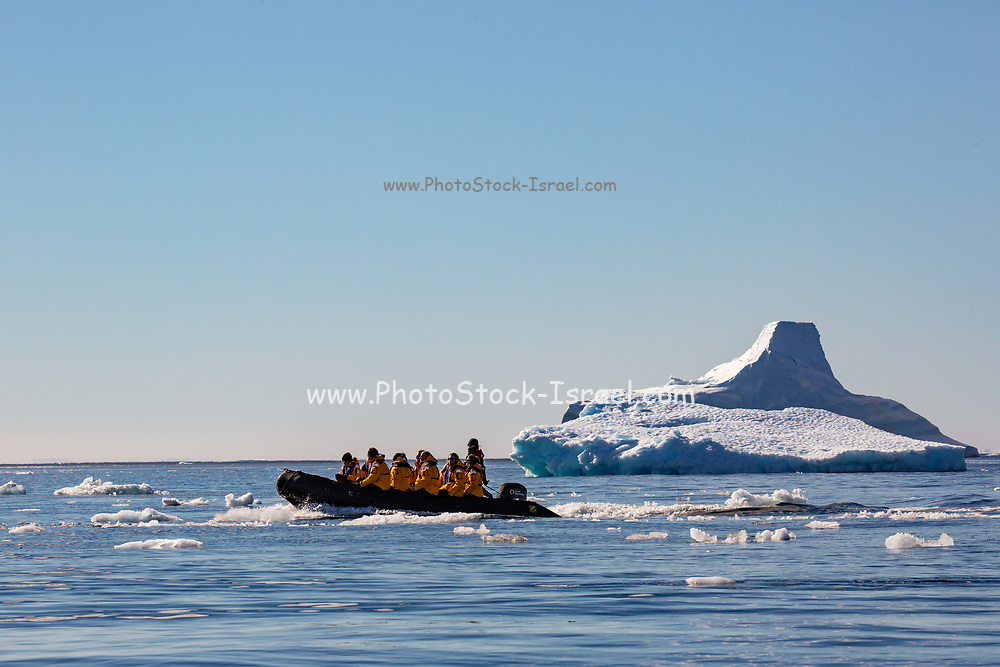 tourists on a rubber Zodiac dinghy sailing through ice floe in the cold waters of Antarctica