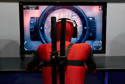 © Licensed to London News Pictures.  27/09/2012. LONDON, UK. A visitor dressed as character Deadpool tries out an unreleased computer game at the Eurogamer Expo in Earls Court London. The show opened today (Thursday) and 50,000 people are expected to attend over the next 4 days. Photo credit :  Cliff Hide/LNP