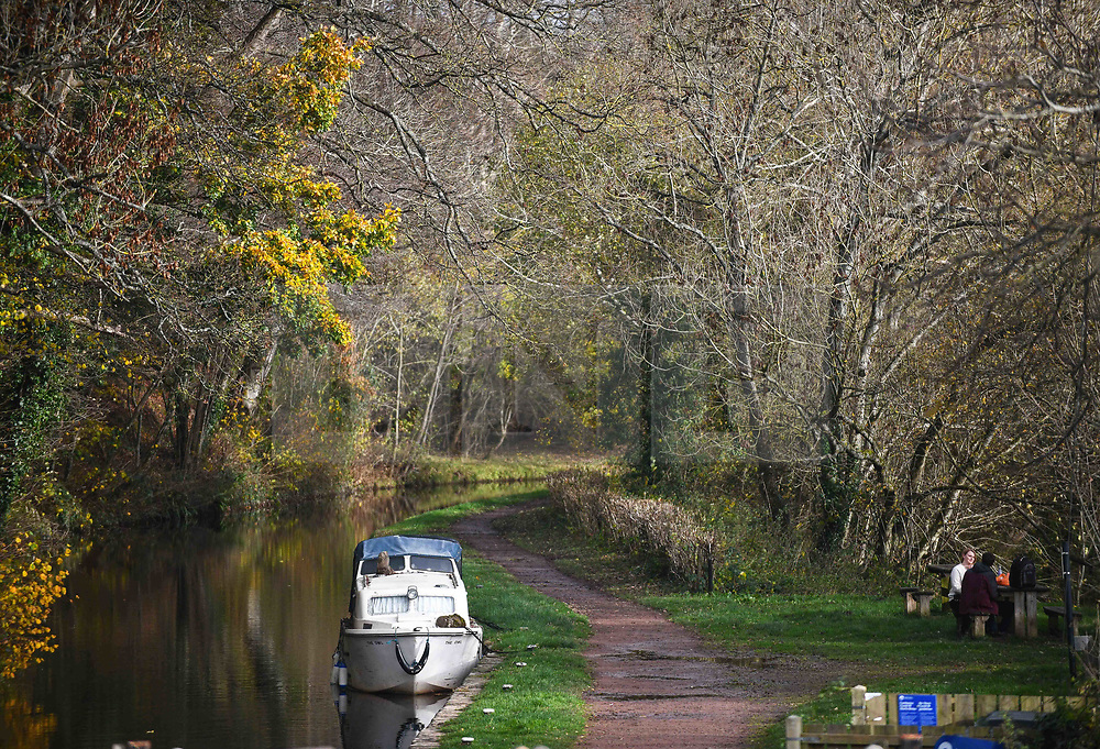 © Licensed to London News Pictures. 17/11/2020. Brecon, UK. People relax on the banks of the Monmouthshire and Brecon Canal in Brecon, Wales on a typical Autumn day as blustery and wet weather grips the UK and is forecast to remain throughout the week. Photo credit: Robert Melen/LNP