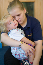 Nursery Nurse comforting a toddler who is crying,