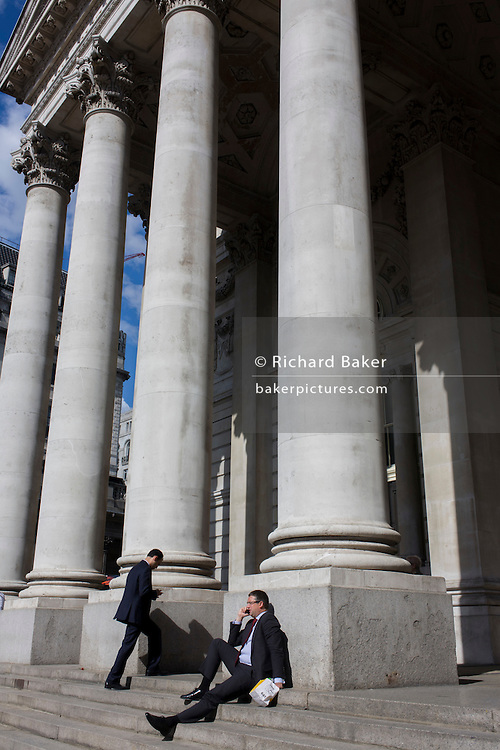 Businessmen beneath Cornhill pillars in the City of London.