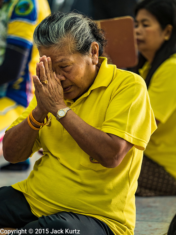 05 DECEMBER 2015 - BANGKOK, THAILAND:  A woman prays for the King in the lobby at Siriraj Hospital on the 88th birthday of Bhumibol Adulyadej, the King of Thailand. Hundreds of people crowded into the plaza hoping to catch a glimpse of the revered Monarch. The King has lived at Siriraj Hospital off and on for more than four years.    PHOTO BY JACK KURTZ