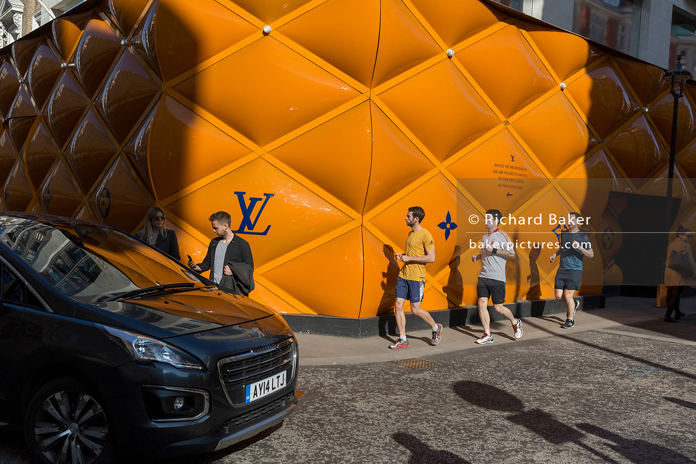 Three runners pass the temporary renovation hoarding of luxury brand Louis Vuitton in New Bond Street, on 27th February 2019, in London, England.