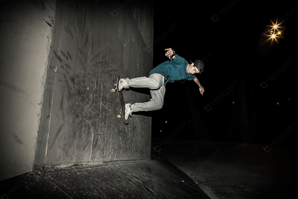 Skateboarder in urban jumping on concrete wall at night