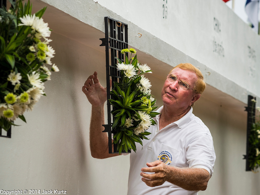 26 DECEMBER 2014 - MAE KHAO, PHUKET, THAILAND: PAT JAMES, an American living in Phuket, hangs a wreath of flowers at the Tsunami Memorial Wall in Mae Khao, Phuket. The wall is located at the site that was used as the main morgue for people killed in the tsunami and hosts an annual memorial service. Nearly 5400 people died on Thailand's Andaman during the 2004 Indian Ocean Tsunami that was spawned by an undersea earthquake off the Indonesian coast on Dec 26, 2004. In Thailand, many of the dead were tourists from Europe. More than 250,000 people were killed throughout the region, from Thailand to Kenya. There are memorial services across the Thai Andaman coast this weekend.    PHOTO BY JACK KURTZ