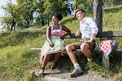 Teenage friends relaxing outdoors on park bench during picnic, Bavaria, Germany