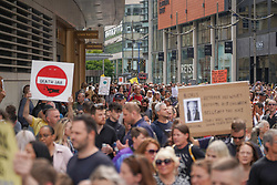 © Licensed to London News Pictures. 24/07/2021. Manchester, UK. Protesters hold banners and shout slogans as they march through the streets of Manchester during an anti-lockdown protest. Photo credit: Ioannis Alexopoulos/LNP