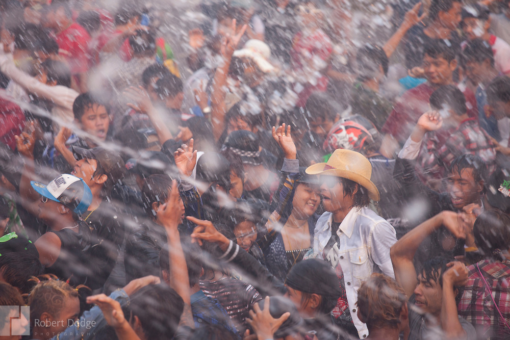 Mandalay, Myanmar- April 14, 2013: Thousands of young people pour into the streets of Mandalay to dance and get hosed by water during Myanmar's Thingyan Water Festival. Thingyan is held in April, one of the hottest months of the year in Myanmar. The water festival marks the country's New Year celebration and the festival includes lots of drinking, singing, dancing and theater. Wherever you are you are likely to get doused with water as the Burmese see this as a cleansing of the previous year's sins and bad luck and a blessing for good luck and prosperity in the year ahead. In the major cities of Mandalay and Yangon, large platforms are erected along major roadways and are equipped with high powered water hoses. The platforms, sponsored by large corporate donors, also have dance stages and play the latest pop and hip hop music. Thousands of residents pour into the streets by foot, motorbike and flatbed truck to get hosed under the platforms while they drink and dance. Many of the young celebrants wear their best clubbing clothes. And many of the party goers are men, having left their wives and girlfriends at home.