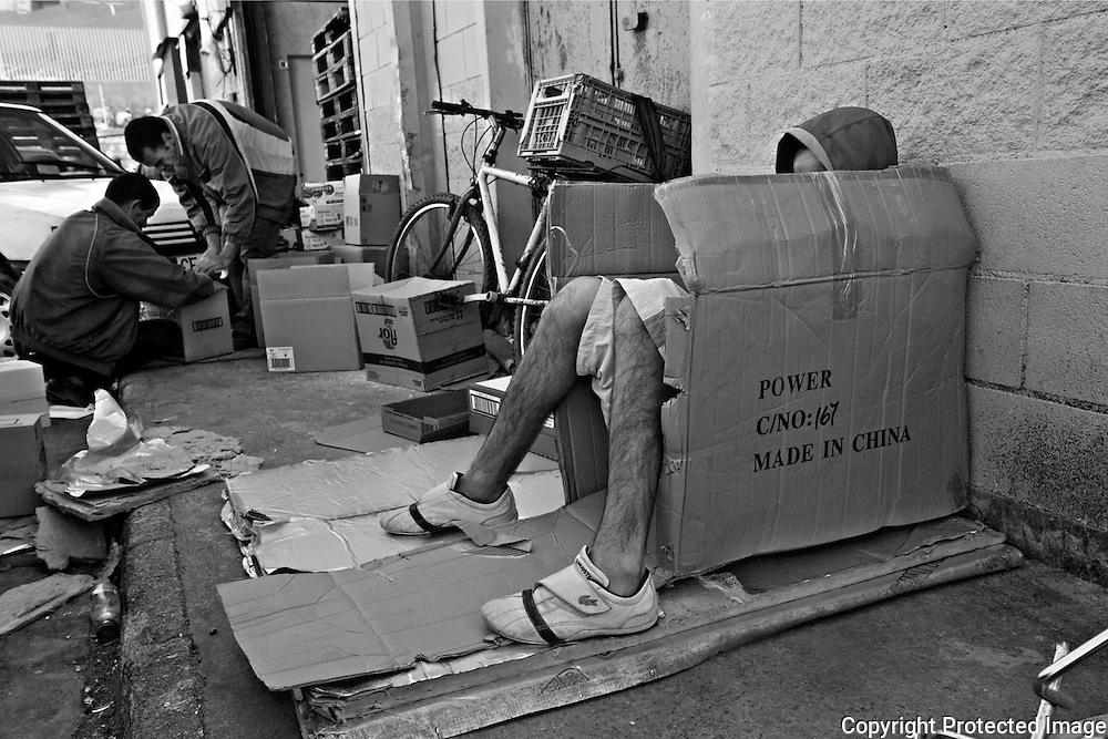 CEUTA, SPAIN - JUNE 27, 2010 : A carrier is sheltered from the cold in the morning while two men  preparing goods to transport at the warehouses located around the pedestrian cross border of El Biutz. Thousands  of people are involved in transporting smuggled goods from Ceuta (an Spanish enclave on the North African coast) to Morocco, it is estimated that every day enter 10.000 porters, mostly women, that it make between three and five trips to Morocco with all types of products purchased on  the warehouse border area of El Biutz in Ceuta, Spain .( Photo by Jordi Cami )