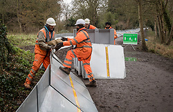 © Licensed to London News Pictures. 01/02/2021. Weybridge, UK. Workers begin installing flood defences along the river Thames at Weybridge in Surrey. Extra precautionis being taken because In 2014 Weybridge and the surrounding area was badly hit by flooding. Photo credit: Ben Cawthra/LNP