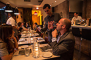 New York, NY, Sept. 30, 2013. Grant Reynolds, wine director at Charlie Bird, looking on as patron Leon Rossi tastes his Montevitrano Agliancio. His companion  Laura Fuentes looks on..