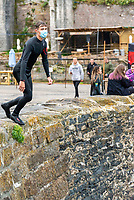 Facemask Tombstoning off the Port Walls in Charlestown near St Austell Bay Cornwall  photo Mark anton Smith