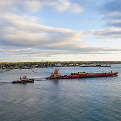 Aerial view of a tugboat and cargo ship in Casco Bay in Portland, Maine.