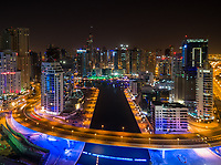 Aerial view of illuminated skyscrapers and canal in Dubai at night, U.A.E.