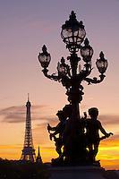 France, Paris (75), les rives de la Seine, classées Patrimoine Mondial de l'UNESCO, sculpture du pont Alexandre III avec la Tour Eiffel illuminée (SETE-illuminations Pierre Bideau) en arrière-plan // France, Paris, Alexandre III bridge and Eiffel Tower at night