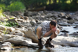 hiker taking a drink of water from a stream in Upstate New York