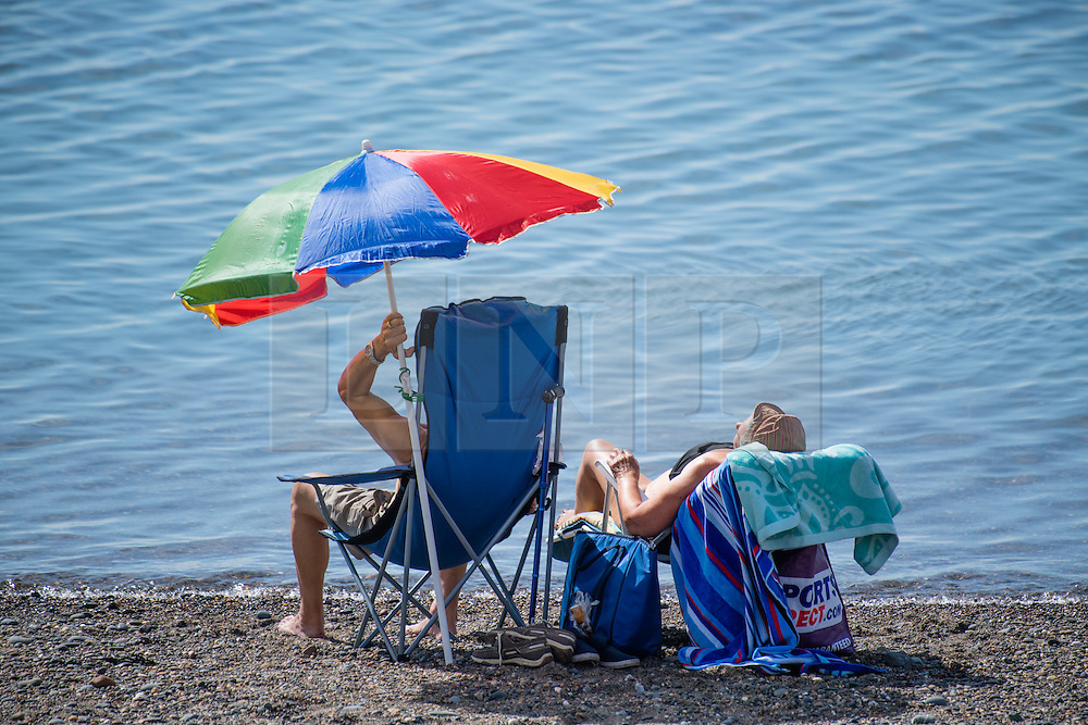 © London News Pictures. 16/08/0216. Aberystwyth, UK. People enjoying a hot summer afternoon at Aberystwyth on the west wales coast. The weather is set to improve even more tomorrow, culminating in a mini-heatwave, with temperatures forecast to reach the high 20s or low 30s centigrade in parts of the UK. Photo credit: Keith Morris/LNP