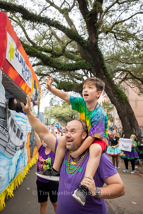 Riley Eagan reaches for beads from the shoulders of his dad, Pat Eagan, as the Krewe of Sparta parades through uptown New Orleans.