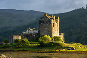 Sunset at Eilean Donan Castle, in Kintail National Scenic Area, Scotland, United Kingdom, Europe. This picturesque island stronghold sits where three sea lochs meet at the village of Dornie in the western Highlands (Loch Duich, Loch Long, and Loch Alsh). Since restoration of the 1200s castle in the early 1900s, a footbridge connects the island to the mainland. The island is named after Donnán of Eigg, a Celtic saint martyred in 617. The castle was founded in the 1200s and became a stronghold of the Clan Mackenzie and their allies the Clan Macrae. In the early 1700s, the Mackenzies' involvement in the Jacobite rebellions led in 1719 to the castle's destruction by government ships. Lieutenant-Colonel John Macrae-Gilstrap's 1920-32 reconstruction of the ruins made the present buildings.