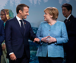 France's President Emmanuel Macron jokes with Chancellor of Germany Angela Merkel during a family photo with representatives from G7 leaders, outreach countries and international organizations at the G7 leaders summit in La Malbaie, Quebec on June 9, 2018. Photo by Justin Tang/CP/ABACAPRESS.COM