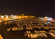 Boats at moorings illuminated by orange glow of streetlights in the marina at the harbour at Faro, Algarve, Portugal